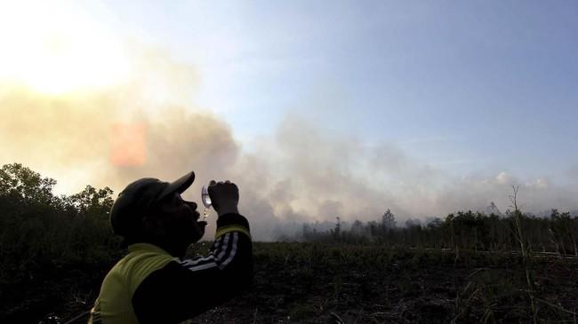 Seorang warga yang kehausan meminum air seusai memadamkan kebakaran hutan dan lahan di Desa Teluk Makmu, kecamatan Medang Kampai, Dumai. Riau. Sabtu (16/3). (ANTARA FOTO/Aswaddy Hamid)