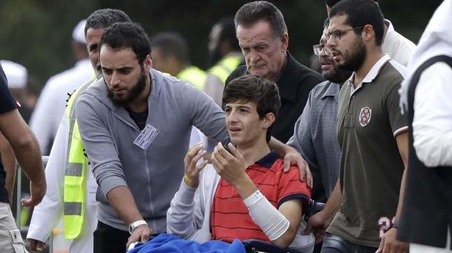 Zaed Mustafa (berkaus merah) kehilangan saudara dan ayahnya, Hamza dan Khalid Mustafa, dalam kejadian itu. Dia juga luka-luka terkena tembakan. (AP Photo/Mark Baker)