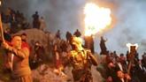 Orang-orang di Akre menadaki gunung dengan membawa obor. Mereka akan menyalakan api besar di puncak gunung itu. Gunung pun terlihat bercahaya. (REUTERS/Ahmed Jadallah)