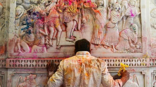 Di sebuah kuil di New Delhi, India, tubuh seorang pemeluk agama Hindu terkena serbuk warna-warni saat mengikuti festival Holi atau festival warna menyambut musim semi. (Photo by Dominique FAGET / AFP)