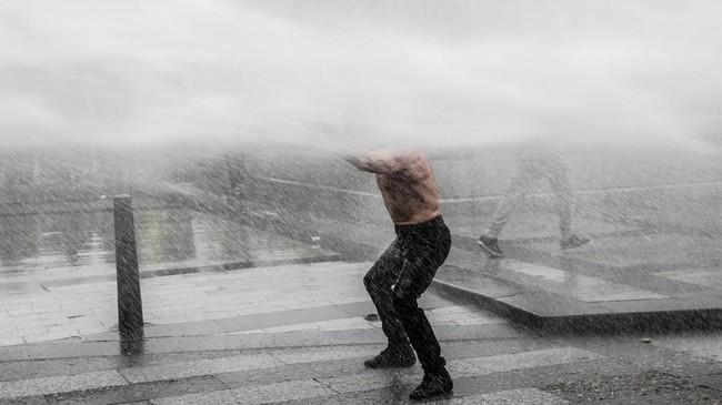 Seorang pria demonstran Rompi Kuning disembur oleh meriam air di jalanan kota Paris. Untuk 18 pekan berturut-turut demonstrasi Rompi Kuning digelar untuk memprotes berbagai kebijakan pemerintah Perancis. (Photo by Geoffroy VAN DER HASSELT / AFP)