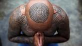 Seorang penganut kepercayaan menghadiri festival tato di biara Wat Bang Phra, Provinsi Nakhon Pathom, Thailand. Mereka meyakini tato memiliki kekuatan mistis. (REUTERS/Athit Perawongmetha)