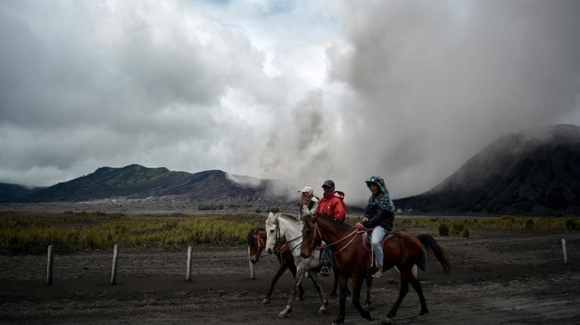 Tiga orang menunggang kuda dengan latar belakang Gunung Bromo yang menyemburkan abu vulkanis di Probolinggo, Jawa Timur, 15 Maret 2019. (ANTARA FOTO/Umarul Faruq)