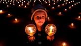 Seorang bocah perempuan menyalakan lilin dan menghadiri acara yang menyebarkan pesan kedamaian pada dunia di Kathmandu, Nepal. (REUTERS/Navesh Chitrakar)