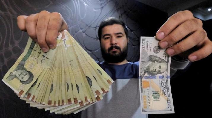 FOTO FILE: Penukar mata uang berpose untuk kamera dengan uang seratus dolar AS (R) dan jumlah yang diberikan ketika mengubahnya menjadi real Iran (L), di toko penukaran mata uang di kawasan bisnis Teheran, Iran, 20 Januari 2016 REUTERS / Raheb Homavandi / TIMA