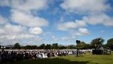 Di sekeliling jemaah diberi pagar pembatas. Warga non-muslim Selandia Baru yang hadir menyaksikan salat Jumat berkumpul di luar pagar. (REUTERS/Edgar Su)