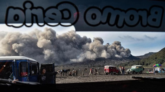 Di tengah-tengah aktivitas vulkanis Gunung Bromo meningkat, sektor pariwisata tetap berjalan seperti biasa. Jip pengantar wisataterparkir di lautan pasir ketika wisatawan melihat abu vulkanik menyembur dari kawah Gunung Bromo di Jawa Timur, Jumat (22/3). (ANTARA FOTO/Widodo S Jusuf)