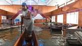 Warga menggunakan perahu memasuki gereja yang terendam banjir akibat meluapnya Danau Sentani. Banjir juga mengganggu pelaksanaan ibadah di gereja tersebut. Belum diketahui jumlah kerugian akibat banjir yang merusak gereja. (ANTARA FOTO/Zabur Karuru)