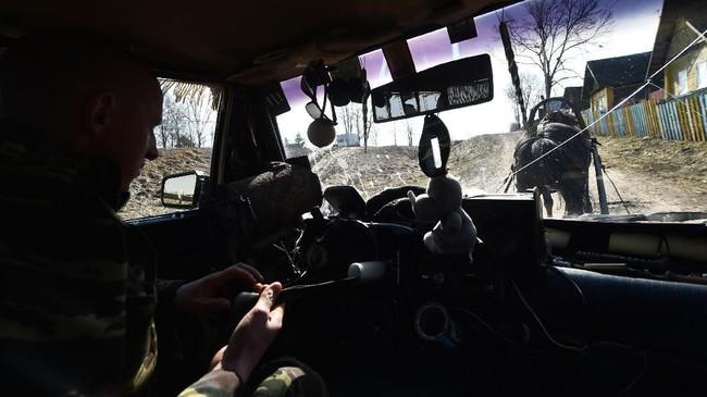 Meski ia memotong mobilnya setengah, ia tetap mempertahankan bagian setir dan tetap memfungsikan klakson mobil(Photo by Sergei GAPON / AFP)