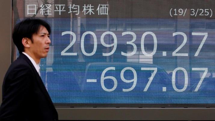 A man stands in front of an electronic board showing the Nikkei stock index outside a brokerage in Tokyo, Japan, March 25, 2019. REUTERS/Kim Kyung-hoon