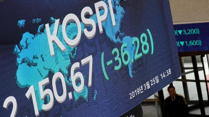 A woman walks past an electronic board showing the Korea Composite Stock Price Index (KOSPI) at the Korea Exchange in Seoul, South Korea, March 25, 2019.    REUTERS/Kim Hong-Ji