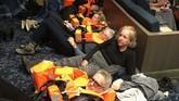 Sejumlah penumpang sudah mengenakan pelampung saat menunggu bantuan di dalam kapal pesiar Viking Sky. (Alexus Sheppard via AP)