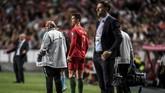 Dalam perjalanan meninggalkan lapangan Cristiano Ronaldo melihat para pemain timnas Portugal ketika berjuang melawan Serbia. (PATRICIA DE MELO MOREIRA / AFP)