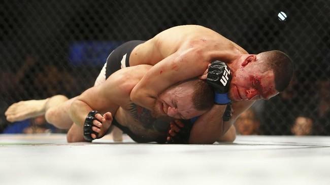 Conor McGregor menelan kekalahan pertama di UFC di tangan Nate Diaz pada pertarungan di Las Vegas, 5 Maret 2016. Meski mendominasi pertarungan ronde pertama, McGregor kalah submission di ronde kedua. (Rey Del Rio/Getty Images/AFP)