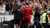 Cristiano Ronaldo berbicara dengan pelatih timnas Portugal Fernando Santos sebelum meninggalkan lapangan karena cedera hamstring. (REUTERS/Rafael Marchante)