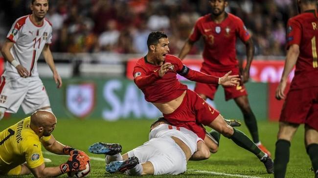 Cristiano Ronaldo berjibaku dengan bek Serbia Nikola Milenkovic. Ronaldo sempat mendapat sejumlah peluang sebelum mengalami cedera. (PATRICIA DE MELO MOREIRA / AFP)