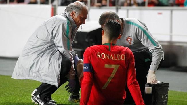 Dua anggota tim medis timnas Portugal langsung menghampiri Cristiano Ronaldo. Dalam tayangan ulang terlihat Ronaldo mengeluh sakit di bagian paha kanan. (REUTERS/Rafael Marchante)