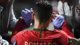 Dua anggota tim medis timnas Portugal berusaha membantu Cristiano Ronaldo berdiri setelah digantikan Pizzi. (PATRICIA DE MELO MOREIRA / AFP)