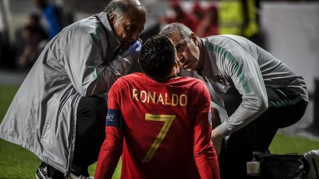 Cristiano Ronaldo terlihat kesakitan ketika dokter memegang paha kanan. Pelatih Fernando Santos kemudian mengganti Ronaldo dengan Pizzi pada menit ke-30. (PATRICIA DE MELO MOREIRA / AFP)