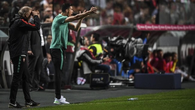 Menariknya Cristiano Ronaldo kembali ke pinggir lapangan untuk mendukung timnas Portugal. Tidak jarang Ronaldo memberi instruksi kepada tim seperti yang CR7 lakukan pada final Piala Eropa 2016 melawan Prancis. (PATRICIA DE MELO MOREIRA / AFP)