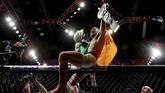 Conor McGregor merayakan gelar juara dunia kelas ringan UFC setelah menang TKO di ronde kedua atas Eddie Alvarez di Madison Square Garden, 12 November 2016. (Michael Reaves/Getty Images /AFP)