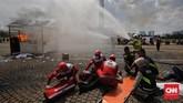 Petugas pemadam kebakaran melakukan simulasi pemadaman api saat hari pencoblosan. (CNNIndonesia/Adhi Wicaksono)