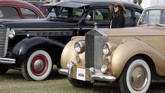 Seorang wanita berdiri di antara model lawas Buick berwarna hitam dan Rolls-Royce Silver Dawn pada acara ke-7 Cairo Classic Meet 2019 di Kairo, Mesir pada 23 Maret 2019. (REUTERS/Mohamed Abd El Ghany)