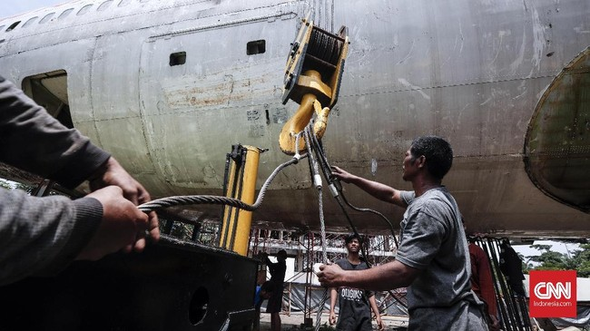 Menggunakan alat berat untuk memindahkan posisi pesawat sesuai pesanan. (CNN Indonesia/Safir Makki)