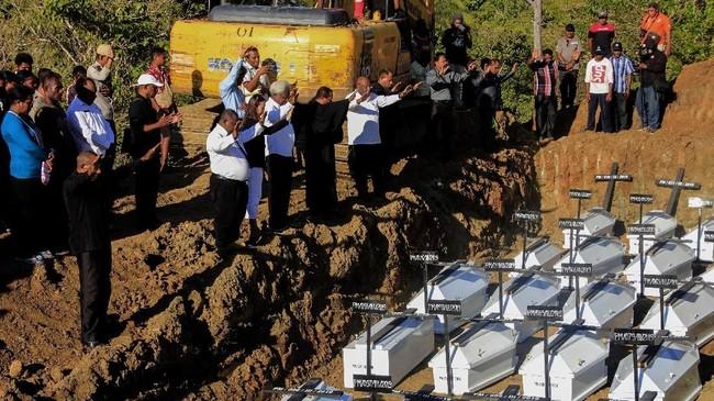 Warga melakukan ibadah ketika memakamkan jenazah korban banjir bandang Sentani yang dikuburkan secara massal di Pemakaman Umum Kampung Harapan Sentani, Jayapura, Papua, Rabu (27/3/2019). Sebanyak 20 jenazah yang belum teridentifikasi dikuburkan secara amassal. ANTARA FOTO/Gusti Tanati/wpa/ama.