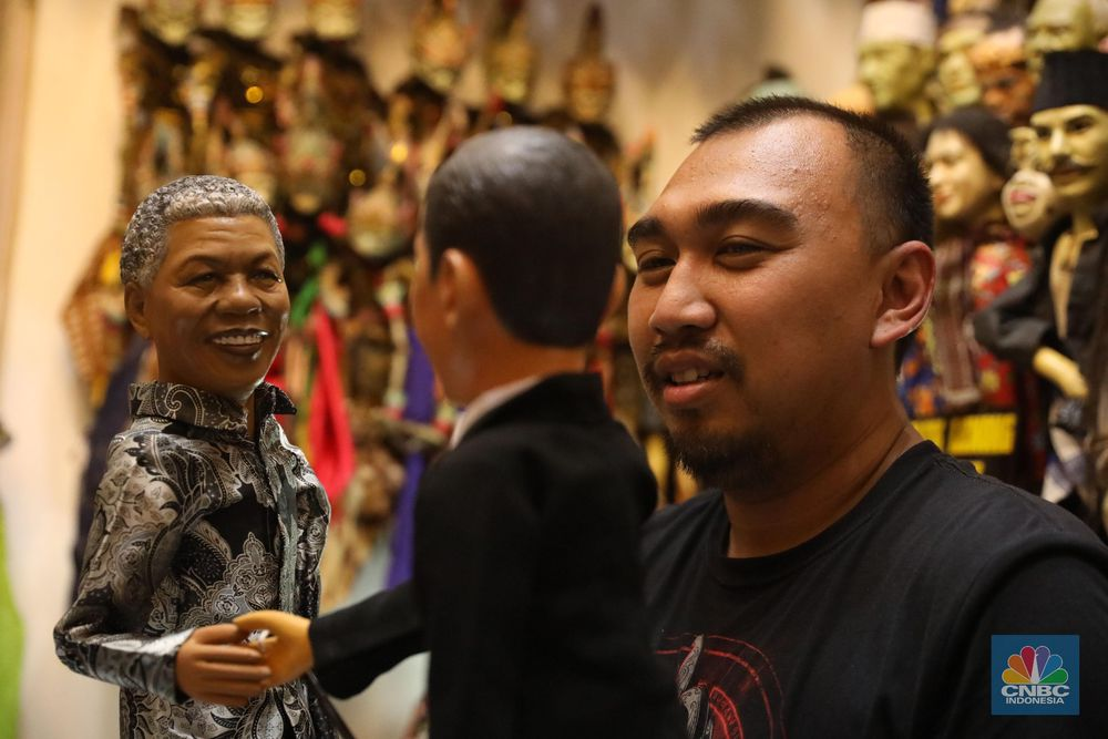 Dalang wayang kebudayaan Reza Purbaya memegang wayang bersama koleksi wayang miliknya di Kawasan Sunter, Jakarta, Kamis, (28/3). Reza merupakan dalang wayang Betawi yang juga memiliki ribuan koleksi wayang custom dari berbagai jenis dan daerahnya. (CNBC Indonesia/Muhammad Sabki)