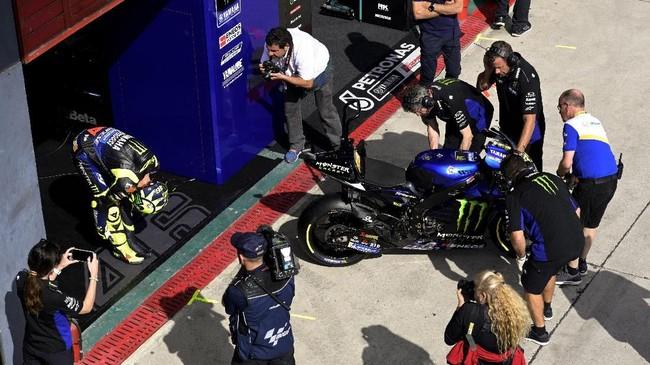 Valentino Rossi melakukan peregangan sebelum meninggalkan garasi Yamaha. Rossi sempat terpuruk di posisi sepuluh pada latihan bebas pertama MotoGP Argentina 2019. (JUAN MABROMATA / AFP)