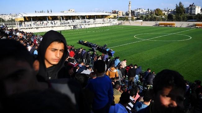 Para penggemar sepakbola dan staf tim berdoa di pertengahan waktu pertandingan di antara Rafah dari Gaza Selatan, dengan rival mereka, Beit Hanoun. Fan sepakbola Gaza terbagi menjadi dua seperti halnya Real Madrid dan Barcelona, namun persaingan antar-klub lokal pun tak kalah sengit.(REUTERS/Dylan Martinez)