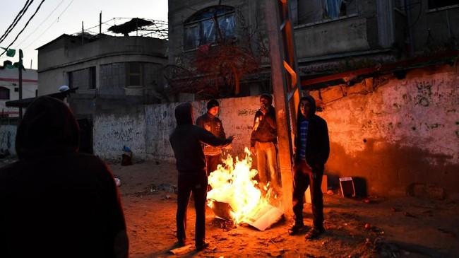 Sekelompok pria pengangguran membakar kardus untuk menghangatkan tubuh kala pagi mulai menjelang di Gaza. (REUTERS/Dylan Martinez)