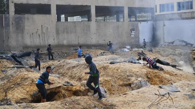 Anak-anak kecil di Gazapunya permainan bernama 'Arab dan Yahudi', di mana mereka membakar kardus-kardus untuk membentuk parit dan saling melempar bola pasir sebagai peluru.(REUTERS/Dylan Martinez)