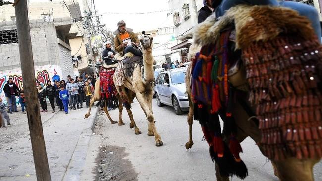Joki Badui berparade bersama unta-unta mereka di jalanan dalam rangka perayaan pesta pernikahan di Gaza. Parade unta adalah hal biasa di Gaza, diadakan oleh pihak pengantin dengan tujuan menghibur para tamu. (REUTERS/Dylan Martinez)
