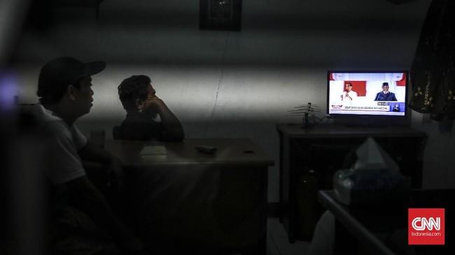 Sejumlah warga Karet Tengsin nonton bareng debat capres keempat di pos keamaan , Jakarta, 30 Maret 2019. Debat keempat capres kali ini membahas tema ideologi, pemerintahan, pertahanan dan keamanan, serta hubungan internasional. (CNN Indonesia/ Hesti Rika)