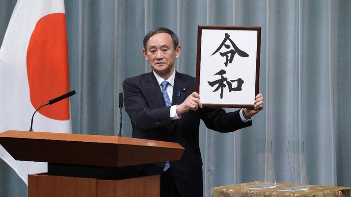 """Japan's Chief Cabinet Secretary Yoshihide Suga unveils the name of new era """"Reiwa"""" at the prime minister's office in Tokyo, Monday, April 1, 2019. Japan says next emperor Naruhito's era name is Reiwa, effective May 1 when he takes the throne from his father.(AP Photo/Eugene Hoshiko)"""
