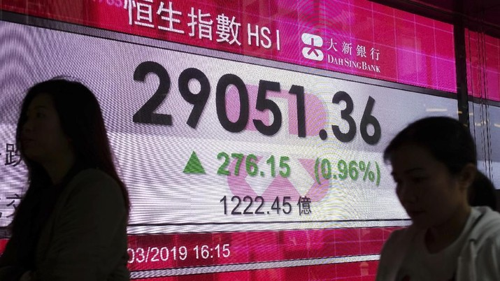A woman walks past an electronic board showing Hong Kong share index outside a local bank in Hong Kong, Monday, April 1, 2019. Shares have surged in Asia following a bullish Friday on Wall Street, where the benchmark S & P 500 logged its biggest quarterly gain in nearly a decade. (AP Photo/Vincent Yu)
