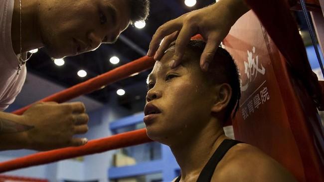 Huang Wensi mendengar pengarahan dari pelatih saat duel menghadapi Jarusiri Rongmuang. (REUTERS/Yue Wu)