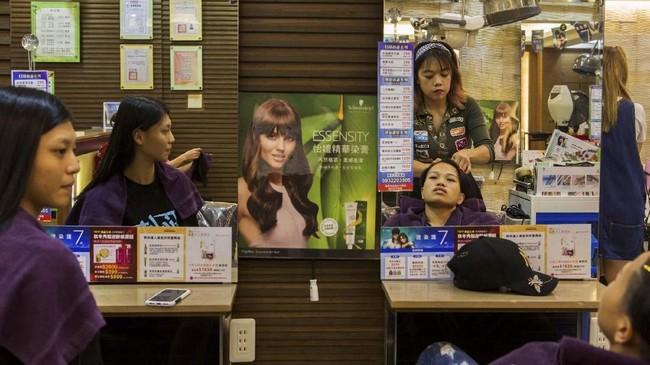 Huang Wensi menata dan menguncir rambutnya, dua hari jelang tampil di tinju kelas Terbang Super Asia. Ia merupakan segelintir dari kaum wanita yang berkecimpung dalam dunia tinju profesional di China. (REUTERS/Yue Wu)