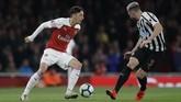 Mesut Oezil mencoba melewati salah satu bek Newcastle United Paul Dummett untuk menciptakan peluang bagi The Gunners. (AP Photo/Kirsty Wigglesworth)