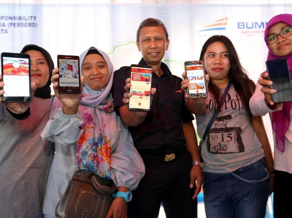 """Deputi PT KAI Daop 1 Jakarta Junaidi Nasution bersama warga menunjukkan aplikasi pembayaran digital LinkAja saat kegiatan Pasar Murah KAI yang bertajuk """"Paket Pangan Murah"""" di Stasiun Bogor, Jawa Barat, Selasa (2/4/2019). Istimewa."""