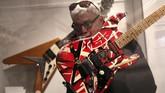 Seorang pria terlihat memeriksa gitar yang dibuat khusus untuk Eddie Van Halen, pendiri band Van Halen yang populer antara lain lewat 'Jump' serta 'Can't Stop Loving You'. (AP Photo/Seth Wenig)