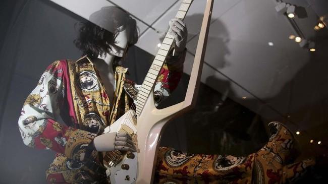 Satu set kostum dan gitar yang sering dipakai oleh Prince, seorang figur musik yang amat disegani sejak 1970-an. Prince meninggal pada April 2016, diduga akibat overdosis obat. (AP Photo/Seth Wenig)