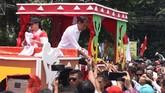Calon Presiden nomer urut 01 Joko Widodo didampingi istri Iriana Joko Widodo menyapa warga dari atas mobil hias diiringi pawai budaya sebagai rangkaian kampanye terbuka di Palembang. (ANTARA FOTO/Feny Selly/hp)