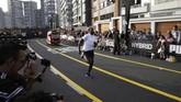 Usain Bolt tampak jauh meninggalkan kendaraan yang familier disebut mototaxi di Peru atau populer dengan sebutan bajaj di Indonesia. (AP Photo/Martin Mejia)
