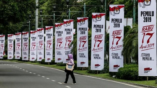 Tampak warga melintas di samping spanduk sosialisasi Pemilu 2019 di Jalan Imam Bonjol, Jakarta, tak jauh dari Kantor KPU Pusat. (ANTARA FOTO/Rivan Awal Lingga/ama)
