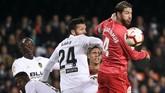 Kapten Real Madrid Sergio Ramos (kanan) berduel dengan bek Valencia Ezequiel Garay. Garay kemudian mencetak gol kedua Valencia pada menit ke-83. (JOSE JORDAN / AFP)