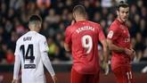 Pemain Real Madrid Gareth Bale (kanan) dan Karim Benzema bereaksi di atas lapangan. Keunggulan 2-1 untuk Valencia bertahan hingga akhir pertandingan. Ini adalah kekalahan pertama Madrid bersama Zinedine Zidane. (JOSE JORDAN / AFP)