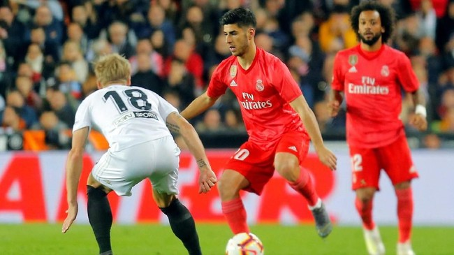 Pemain Real Madrid Marco Asensio berduel dengan pemain Valencia Daniel Wass. Madrid mengincar kemenangan ketiga beruntun sejak Zinedine Zidane ditunjuk sebagai pengganti Santiago Solari. (REUTERS/Heino Kalis)